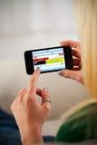 Mulher que usa o iPhone 4 de Apple para consultar o local da notícia Imagem de Stock Royalty Free