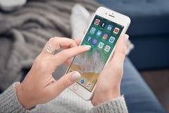 Mulher que usa o iPhone 8 de Apple positivo Imagens de Stock Royalty Free