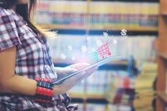 Mulher que usa o laptop com venda em linha ou compra em linha com ícone ou holograma na sala da biblioteca e no fundo da estante imagem de stock royalty free