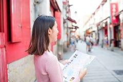 Mulher que usa o mapa da cidade em Macau Imagens de Stock