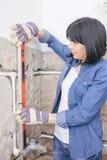 Mulher que usa o nível de água do espírito fotografia de stock royalty free