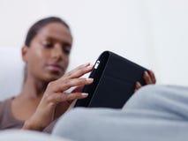 Mulher que usa o PC da tabuleta em casa Fotografia de Stock