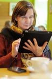 Mulher que usa o PC da tabuleta no café Fotos de Stock