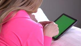 Mulher que usa o PC da tabuleta, tela verde video estoque
