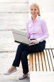 Mulher que usa o portátil ao ar livre imagens de stock