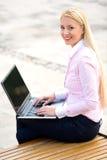 Mulher que usa o portátil ao ar livre fotografia de stock
