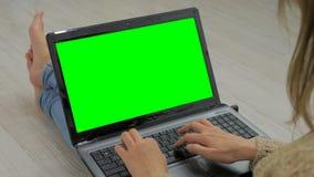 Mulher que usa o portátil com tela verde fotos de stock royalty free