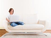Mulher que usa o portátil e bebendo de uma caneca Foto de Stock Royalty Free