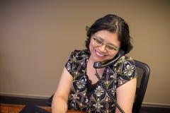 Mulher que usa o portátil e falando na linha terrestre Imagem de Stock