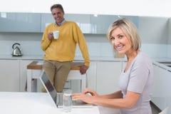 Mulher que usa o portátil e o homem com o copo de café na cozinha Imagem de Stock
