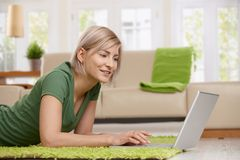 Mulher que usa o portátil em casa Fotos de Stock