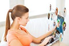 Mulher que usa o portátil em casa imagens de stock