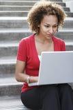 Mulher que usa o portátil em etapas fora fotografia de stock