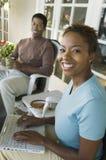 Mulher que usa o portátil, marido no fundo fotografia de stock royalty free