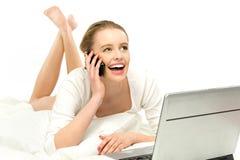 Mulher que usa o portátil na cama Imagens de Stock
