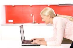 Mulher que usa o portátil na cozinha Fotografia de Stock