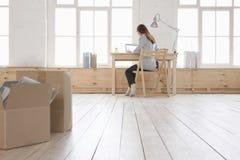 Mulher que usa o portátil na mesa no apartamento do sótão Fotografia de Stock