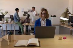 Mulher que usa o portátil na mesa fotografia de stock