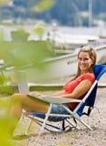 Mulher que usa o portátil na praia Fotos de Stock
