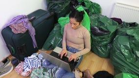Mulher que usa o portátil na sala desarrumado vídeos de arquivo