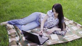 Mulher que usa o portátil no parque filme
