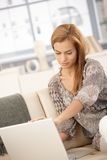 Mulher que usa o portátil no sofá Foto de Stock