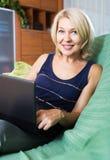 Mulher que usa o portátil no sofá Fotografia de Stock Royalty Free