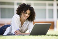 Mulher que usa o portátil no terreno foto de stock royalty free