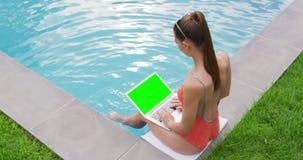 Mulher que usa o portátil perto da piscina no quintal 4k video estoque