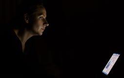 Mulher que usa o portátil tarde na noite imagem de stock