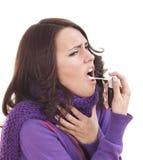 Mulher que usa o pulverizador da garganta. Foto de Stock