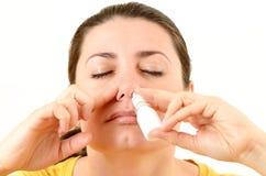 Mulher que usa o pulverizador nasal Fotos de Stock