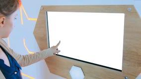 Mulher que usa o quiosque interativo do ?cran sens?vel com a tela vazia branca foto de stock