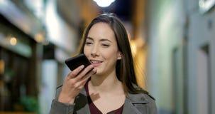 Mulher que usa o reconhecimento de voz do telefone na noite