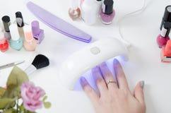 Mulher que usa o secador da luz UV Tratamento de mãos, conceito do salão de beleza dos termas Fotos de Stock