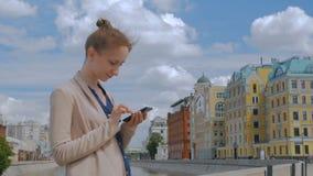 Mulher que usa o smartphone vídeos de arquivo