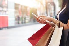 Mulher que usa o smartphone ao guardar sacos de compras imagens de stock