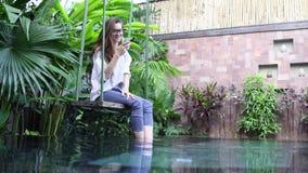Mulher que usa o smartphone ao sentar-se no balanço perto da associação no país tropical vídeos de arquivo
