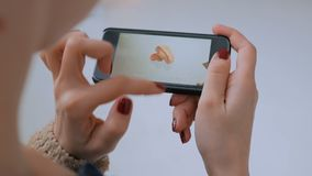 Mulher que usa o smartphone com realidade aumentada app e explorando o modelo virtual