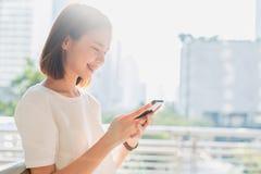Mulher que usa o smartphone, durante o tempo de lazer O conceito de usar o telefone ? essencial na vida quotidiana imagem de stock