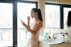 Mulher que usa o smartphone e escovando os dentes no banheiro foto de stock