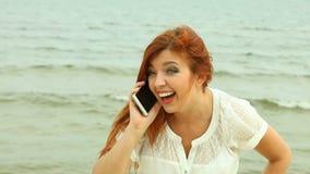 Mulher que usa o smartphone em uma praia Imagem de Stock