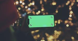 Mulher que usa o smartphone horizontal com tela verde video estoque