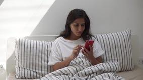 Mulher que usa o smartphone na cama video estoque