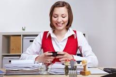 Mulher que usa o smartphone na mesa no escritório foto de stock