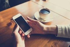 Mulher que usa o smartphone na tabela de madeira no caf? imagem de stock