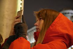 Mulher que usa o smartphone no mercado europeu do Natal foto de stock royalty free