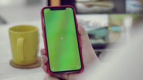 Mulher que usa o smartphone que olha a tela verde no telefone celular, filme