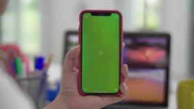 Mulher que usa o smartphone que olha a tela verde no telefone celular, video estoque