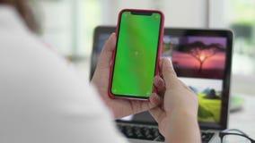 Mulher que usa o smartphone que olha a tela verde no telefone celular, vídeos de arquivo